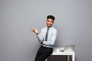 Business Concept - portrait of african american businessman talking and having coffee sitting at a desk using a laptop.