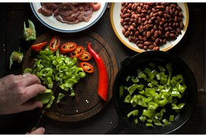 Man cuts green pepper for fajita top view