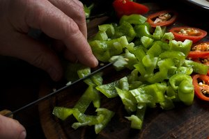 Man cuts green pepper for fajita close-up
