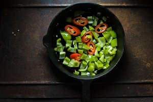Green pepper and chili on a cast-iron frying pan copy space