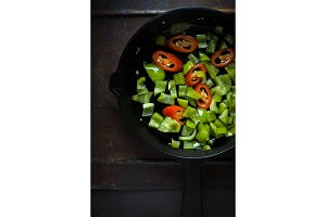 Green pepper and chili on a cast-iron frying pan