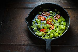 Green pepper and chili on a cast-iron frying pan side view