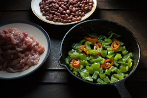 Pieces of chicken, beans. Pepper and chili in a frying pan.