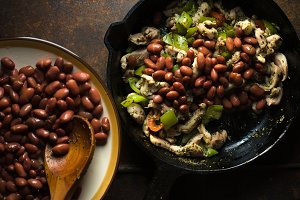 Beans are spread in a frying pan with pepper and chicken closeup