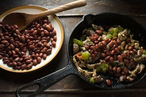 Beans are spread in a frying pan with pepper and chicken side view