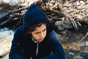 Portrait of teenager sitting on rock near river