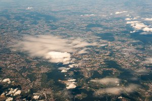 View from airplane on ground with clouds and fields