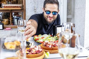 Young man eating Galician octopus