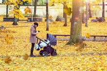 Mother with baby pram in autumn park