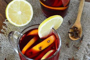 Mulled wine with orange on wooden background