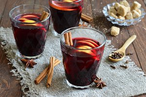 Mulled wine with lemon on wooden background