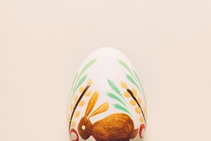 Handpainted Easter egg laying on a c
