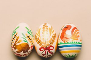 Three handmade Easter eggs on creamy