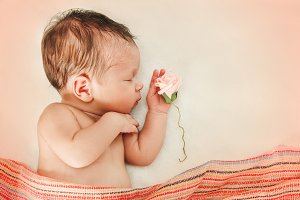Newborn baby girl with flower