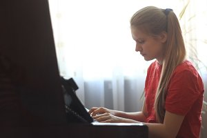 Blonde teenage girl 14-years old playing the piano at home