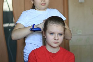 Girls teenagers sisters is making hair for each other at home