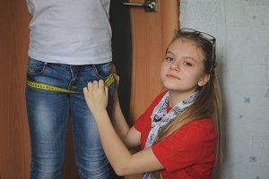 Teen girl 12-years old plays in sewing with sister - seamstress