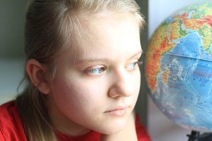 Portrait of young girl teenager at home looking with globe