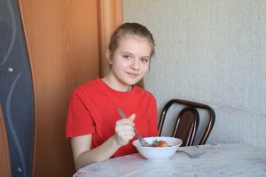 Young teenager girl have breakfast at kitchen - eats buckwheat porridge