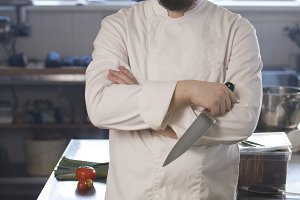 Portrait of a fashionable chef in bandana holding a knife in a kitchen
