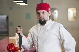 Portrait of a fashionable chef with a knife in bandana
