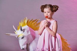 Portrait fashion kid girl. child fashion concept. romantic girl pink. eats a little lollipop.