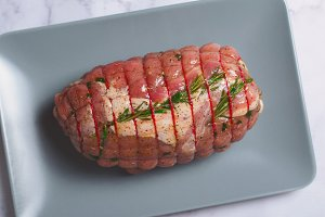 Raw Uncooked Pork, Rolled Meat with Herbs and Seasoning