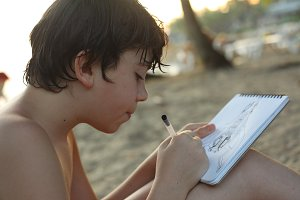 Teenager carefully taking notes in his notebook