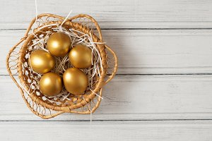Golden eggs in a wooden wicker baske