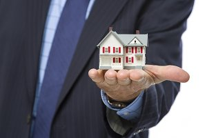 Real Estate Agent Holding Small Hous