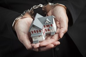 Woman In Handcuffs Holding House