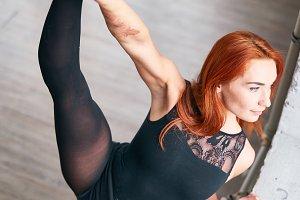 Girl dancer doing stretching near the window