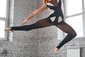 Beautiful ballet dancer posing in dance studio