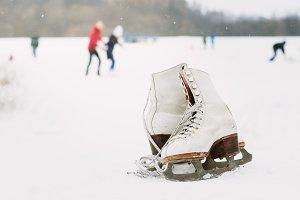 A pair of white retro ice skates.