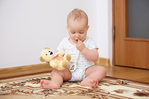 Adorable baby boy playing with toy