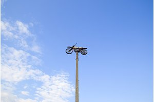 Motorcycle on the pedestal. A light motorbike on a pole, put up