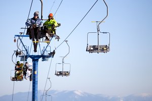 Skiers  climb the lift up mountains