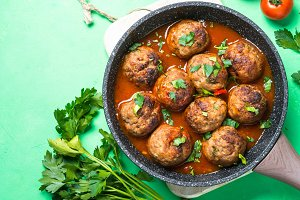 Meatballs in tomato sauce in a frying pan top view.