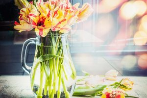 Tulips in glass jug on table