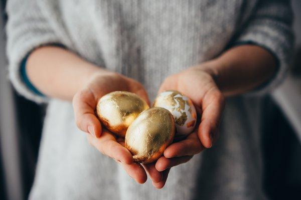 Golden eggs in hands