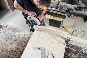 A man builder saws a board