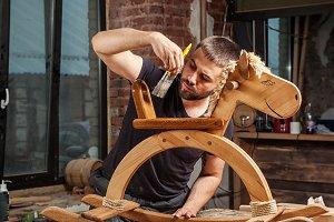 Man paints a wooden toy