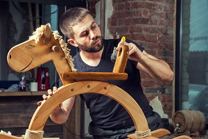 Man paints a wooden toy