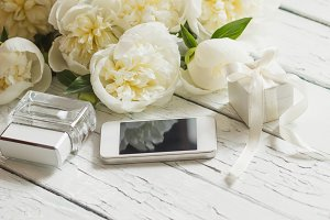 White peonies, phone and gift