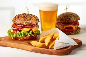 Two burgers with french fries and glass of beer