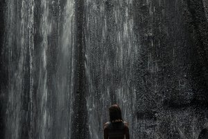 Uoung woman backpacker looking at the waterfall in jungles. Ecotourism concept image travel girl. Bali island, Indonesia.