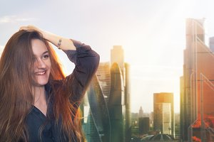 Smiling red-haired girl on the background of skyscrapers of Moscow city.
