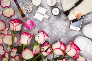 Bouquet of roses with cosmetics in perfume, phone and sneakers on a gray background with copy space