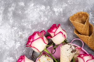 Composition of ice cream waffles with roses bouquets on a stone background