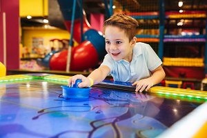 Joyful little boy playing air hockey